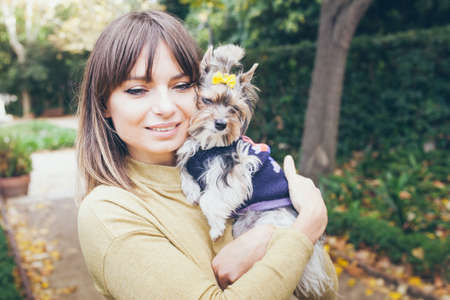 Portrait of a beautiful woman in casual clothes with rare little size purebred dog - Biewer Terrier dress in nice sweater. Love and happiness expression. Standard-Bild