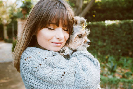 Happy young woman with her little breed dog. Home pets. Young woman is holding and hugging her cute puppy while walking in the park. Outdoor portrait Standard-Bild