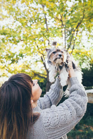 Dog owner and her pet. Happy girl holds with hands up her cute little puppy, feeling happy and expresses love to the dog. Outdoor photo, autumn trees on the background.