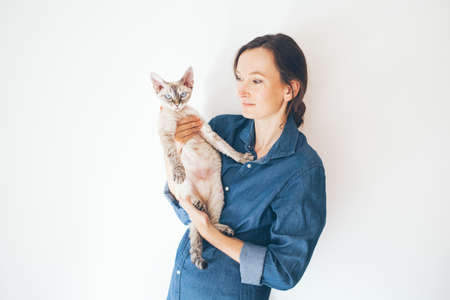Lifestyle photo of a casual dressed woman in blue jeans shirt holding her and Devon Rex cat. Selective focus and natural light