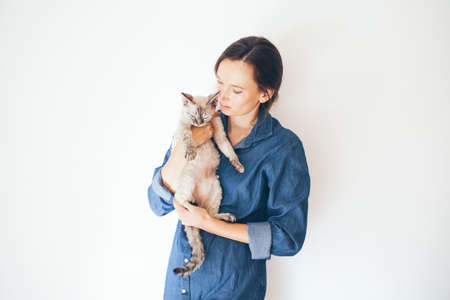 Happy young woman with her Devon Rex cat. Young woman is holding and hugging her cute curious Devon Rex cat. Cat is feeling relaxed and purrs. White wall background.