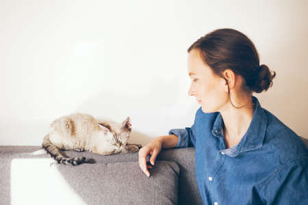 Woman in casual clothes is cuddling her cat. Cat is purring, feeling happy and relaxed. Woman is touching and playing with cute Devon Rex kitty. Lifestyle photo Standard-Bild