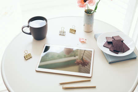 Online education at home concept. Top view of the white color table with tablet, cup of tea and chocolate on it. Lifestyle photo, natural light Standard-Bild