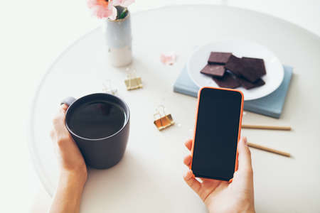 Close-up of woman's hands holding cell phone while drinking tea and eating chocolate. Reading news, surfing the web / internet, chatting in social network in smartphone. Blurred background.