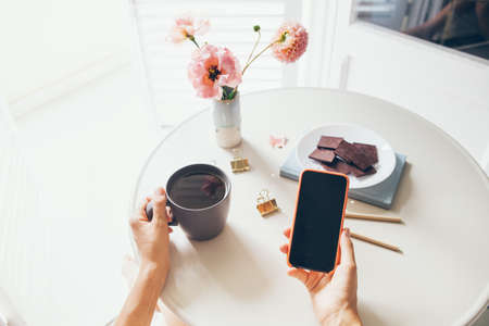 Social distancing, drinking tea and reading news, social network, surfing the web / internet in smartphone staying at home. Remote work, video confidence calls with colleagues.