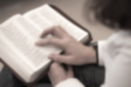 De focused image of a lady reading the holy bible for religion background