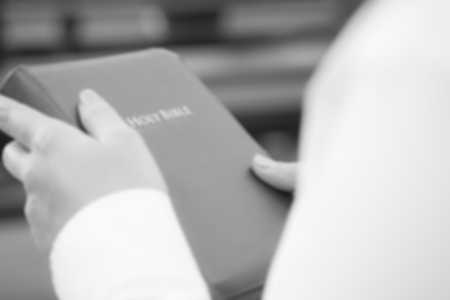 De focused image of a woman holding holy bible in black and white tone
