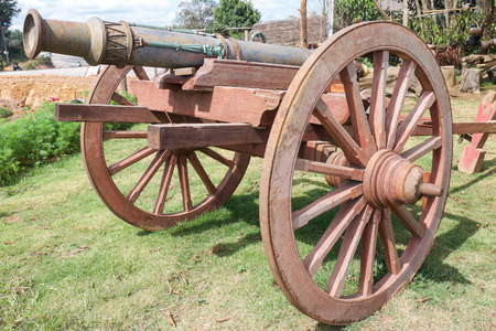 destroying the competition: Ancient or old iron gun with ammunition and wooden wheel stand Stock Photo