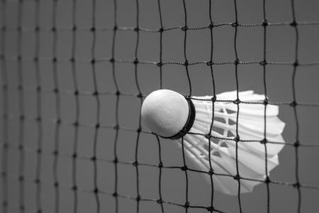 badminton racket: Black and white shuttlecock struck on the net in badminton court