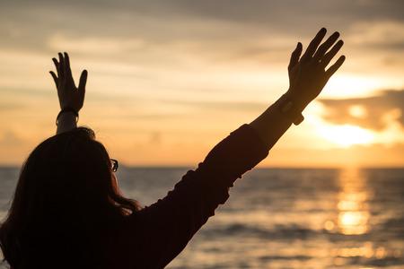 태양 설정 시간에 하늘을 향해 손을 올리는 여자의 실루엣 이미지 스톡 콘텐츠