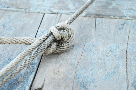 rope: Rope knot on wooden boat plank for sign and symbol background Stock Photo