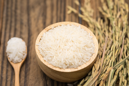 Jasmine rice grains in wooden bowl with dry leaf