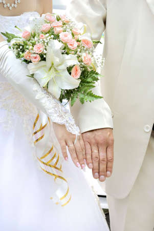 Hands of young marrying pair with a wedding bouquet in a hand of the girl.