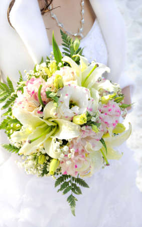 Beautiful white wedding bouquet in hands of the bride. photo