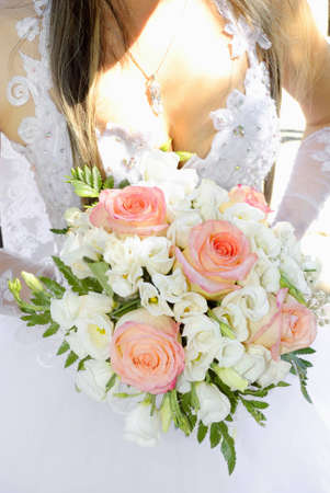 Beautiful white wedding bouquet in hands of the bride. Stock Photo - 12766452