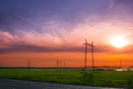 Electricity pylons and wires in a green field against evening sky photo