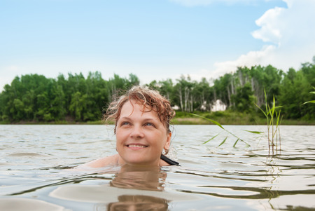 enjoymant: Close up of a womans face swimming in the lake Stock Photo
