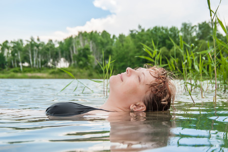 blindly: The woman blindly swims in the lake