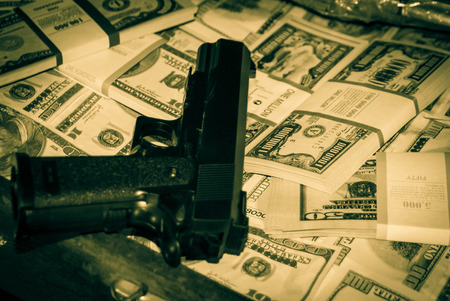 money packs: Black gun on the background of packs with money Stock Photo