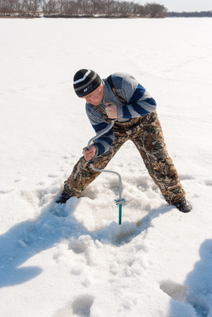 Winter fishing on the river. Young man drill a hole in the ice. Banco de Imagens