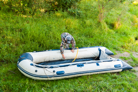 Man is preparing for fishing, inflatable rubber boat pump.
