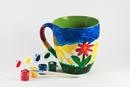 Colorful cup with watercolors and brush Standard-Bild