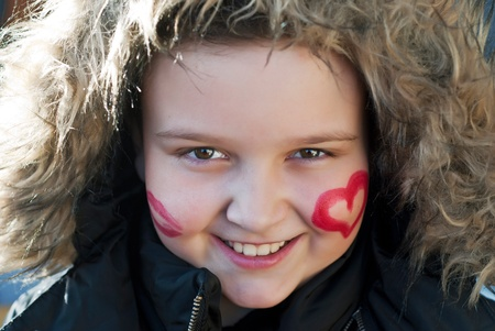 Painted happy child with heart and kiss on cheeks photo