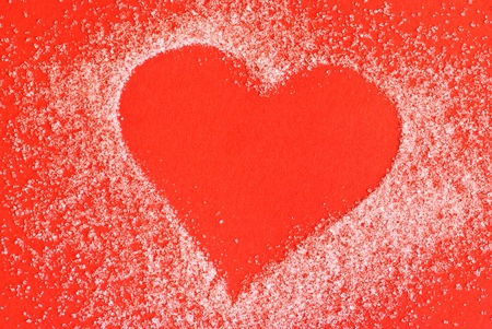 Heart made of sugar on red background photo