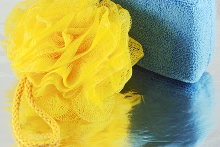 Yellow and blue bath sponge with reflection photo