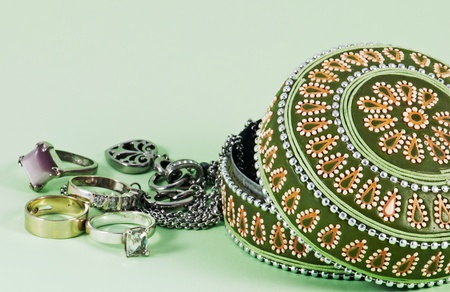 heap of role: Isolated opened jewellery box with rings on green background