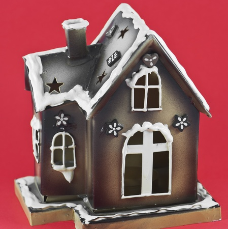 A festively decorated gingerbread house isolated against a red background