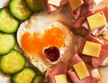Fried egg on heart - shaped toast with cucumber and ham for Valentines Day photo