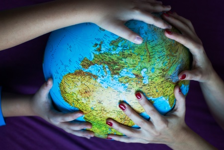 Big globe in four hands Editorial