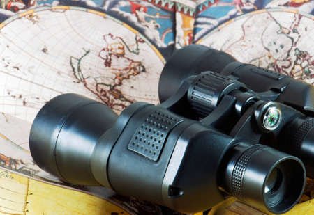 Binoculars on antique map with compass photo