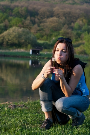 Woman with dandelion by the lake photo