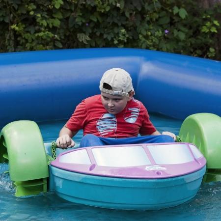 Cute young boy having fun with bumper boats in pool Stock Photo