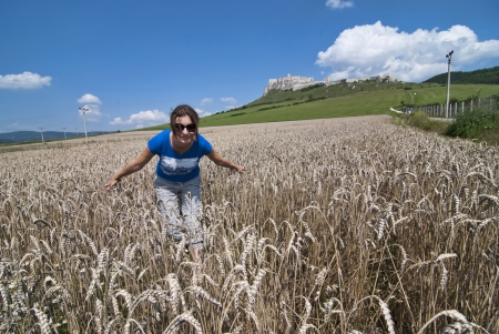 Young woman in sunglasses in wheat field, back is Spis castle Stock Photo