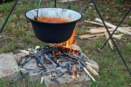 Cooking goulash in a kettle on a fire