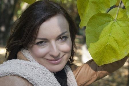 Closeup of a beautiful smiling young woman outdoors under green leaves photo