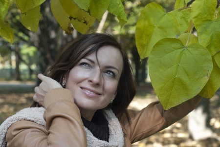 Beautiful young woman with green leaves in autumn Stock Photo - 15895351