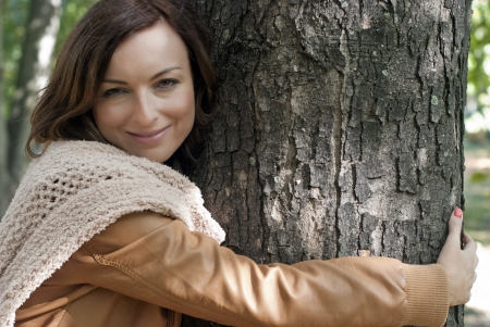 Pretty woman hugging a big tree in a park - outdoor portrait