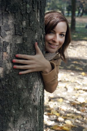 Young smile woman looks out from behind a tree photo