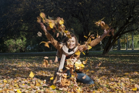 Woman throwing leaves in fall, lifestyle autumn photo