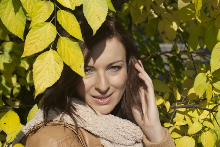 Beautiful woman with yellow leaves looking at me photo