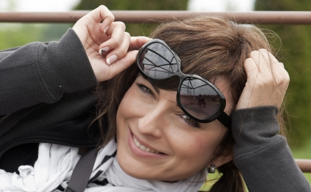 Portrait of smiling young woman outdoors in sunglasses Stock Photo - 15911125