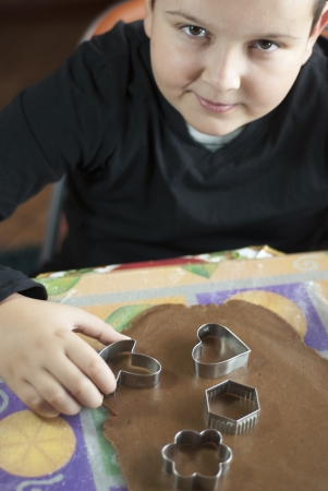 Little boy cutting dough for christmas cookies and look up photo