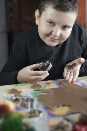 Little boy with two hearts. Cutting gingerbread dough. Stock Photo - 16128974