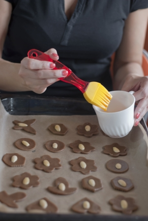 glazing: Glazing christmas cookies before backing with egg. Woman hands.