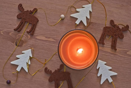 Christmas decoration - trees and a reindeer. Candle flame. photo