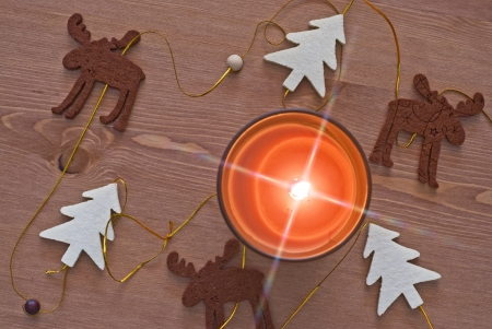 Christmas decoration - trees and a reindeer. Radiant candle flame. photo